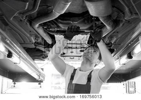 Mid adult automobile mechanic repairing car in workshop