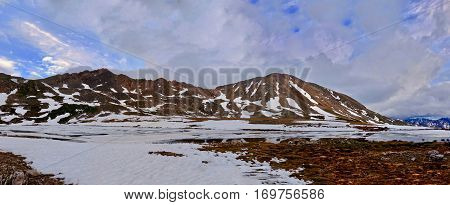 Storm clouds over mountanis and reflection in water. Snow thawing on Independence Pass. Aspen. Colorado. United States.