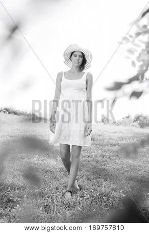 Portrait of young woman in sundress and hat walking in park