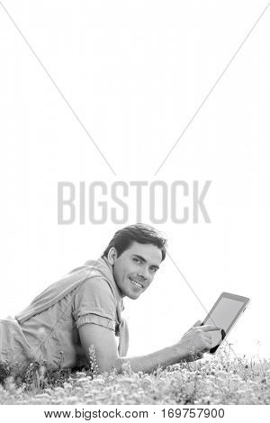 Side view portrait of young man using digital tablet while lying on grass against clear sky