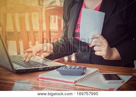 Close up of business woman's hand writing on a notebook and holding a white paper