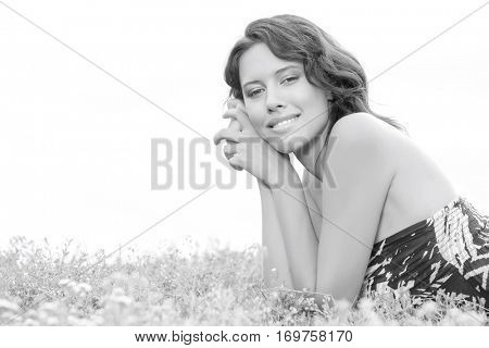 Side view portrait of young woman lying on grass against clear sky