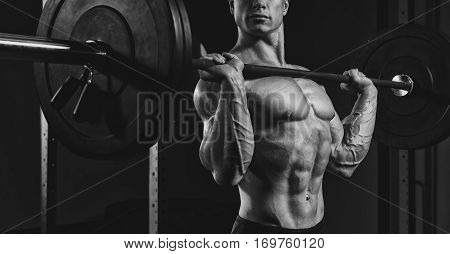 Black and white close up photo of man doing a lifting workout on dark background at gym. Determined male athlete lifting heavy weights.