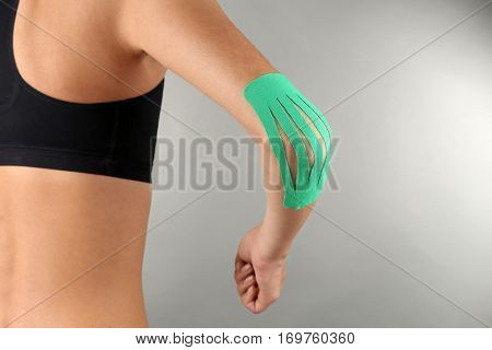 Female elbow with physio tape on gray background