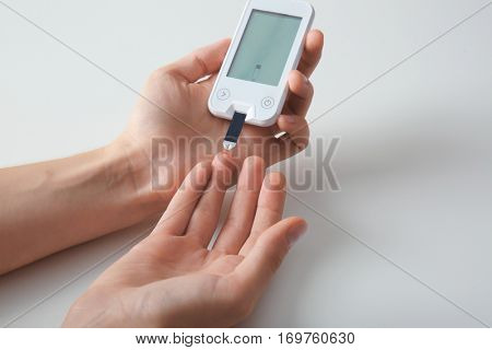 Woman checking blood sugar level by glucometer and test stripe at home