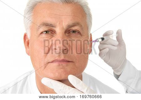 Senior man having correction injection on white background