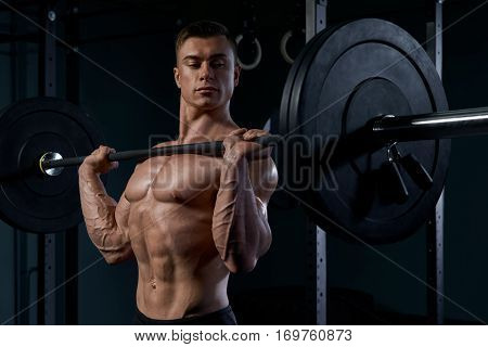 Handsome bodybuilder doing exercise with a barbell at gym. Determined male athlete lifting heavy weights. Man doing a lifting workout on dark background