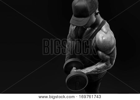 Muscular Bodybuilder Wearing A  Tank Top And Black Cap Doing Biceps Curl With Dumbbell