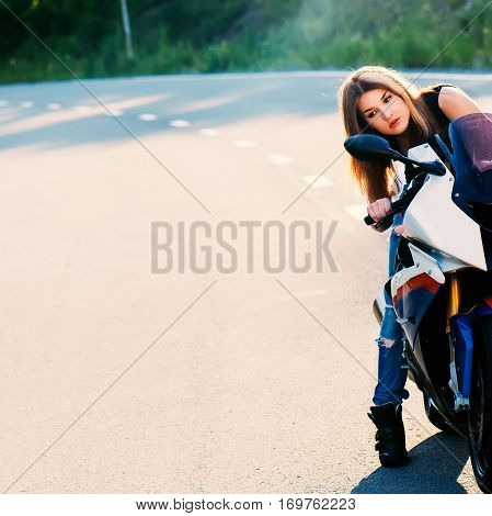 Young beautiful blond woman in fashionable jeans and a black T-shirt looks into the mirror behind the wheel of a modern motorcycle. Outdoor portrait in soft sunlight.