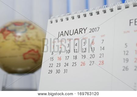 Close up calendar of January 2017 with blur earth globe background