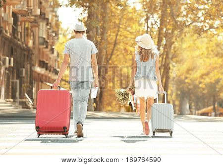 Just married couple with suitcases walking back in the street
