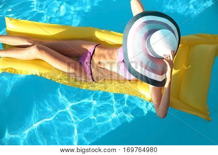 Beautiful young woman relaxing on air mattress in swimming pool