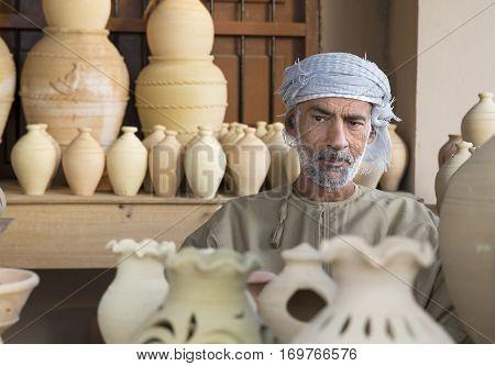 Muscat Oman February 4th 2017: omani man selling clay jars