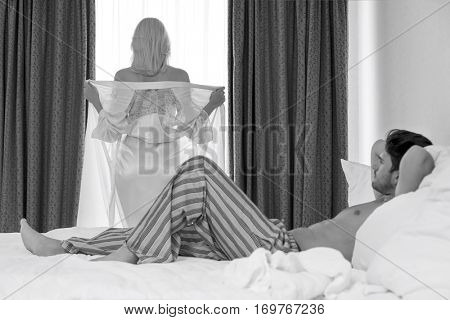 Full length of young man looking at woman removing robe at window
