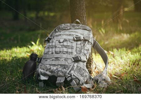 Military bag and canteen on grass near tree, close up view