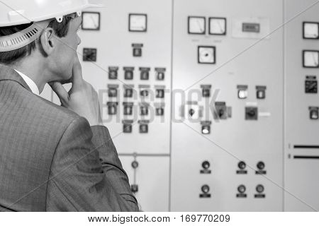 Rear view of male supervisor examining control room in industry