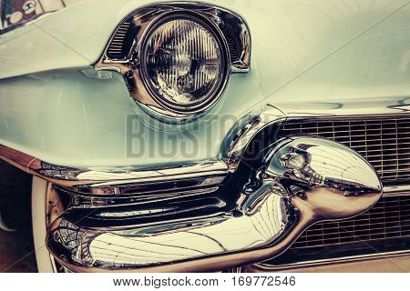 A closeup of the headlights and front bumper on a vintage automobile.