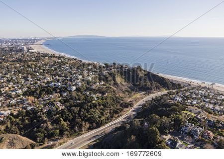 Aerial of Temescal Canyon Road and Pacific Palisades neighborhoods near Santa Monica Bay in Southern California.