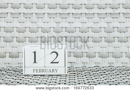 Closeup surface white wooden calendar with black 12 february word on blurred weave wood chair textured background with copy space in selective focus at the calendar