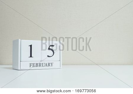 Closeup white wooden calendar with black 15 february word on blurred white wood desk and cream color wallpaper in room textured background with copy space in selective focus at the calendar