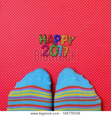 high-angle shot of a pair of feet wearing colorful striped socks and some glittering letters of different colors forming the text happy 2017, on a red surface patterned with white dots