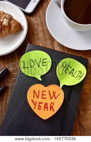 a sticky note with the text new year and two more sticky notes with the words love and health as wishes for the new year attached to a notepad, on a wooden table set for breakfast