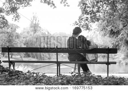Rear view of romantic young couple sitting on bench at lakeside