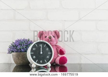Closeup black and white alarm clock for decorate in 12 o'clock with bear doll and plant on black glass table and white brick wall textured background with copy space