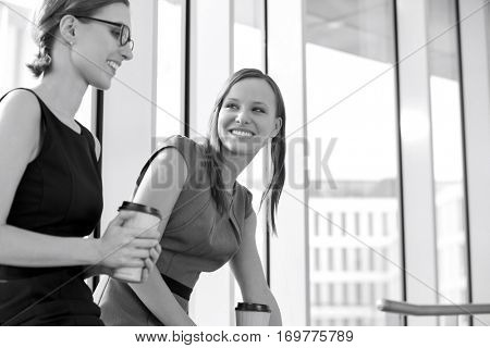 Businesswomen with disposable coffee cups at office