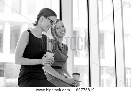 Happy businesswomen with disposable coffee cups at office