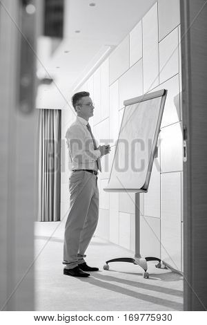 Businessman looking at flipchart in office