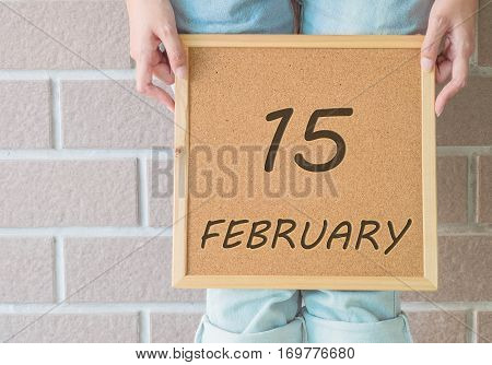 Closeup calendar at the cork board in hand of asian woman in front of her legs with 15 february word on brick wall textured background