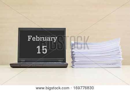 Closeup computer laptop with february 15 word on the center of screen in calendar concept and pile of work paper on wood desk and wood wall in work room textured background with copy space