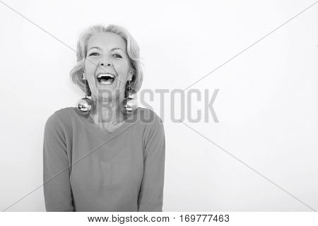 Portrait of senior woman wearing Christmas ornaments over white background