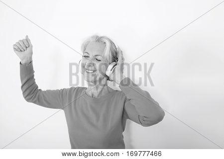 Happy senior woman listening music over white background