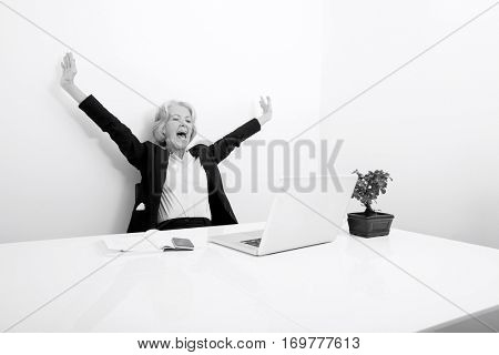 Senior businesswoman yawning while looking at laptop in office