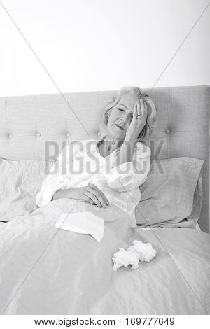 Senior woman suffering from headache resting in bed