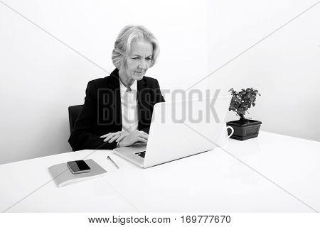 Senior businesswoman using laptop at desk in office