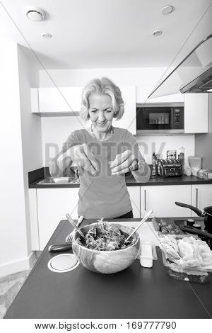 Senior woman preparing salad at kitchen counter