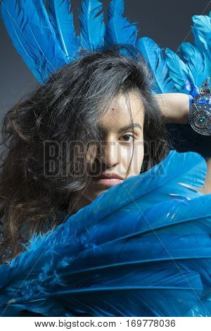 Brunette woman in costume made of blue feathers, wild and free bird, fantasy image