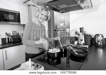 Portrait of happy senior woman cooking food at kitchen counter