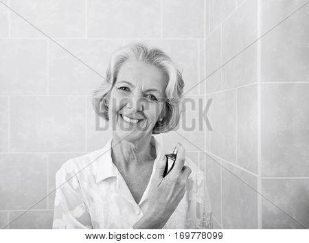 Portrait of happy senior woman spraying perfume in bathroom
