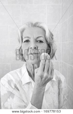 Portrait of senior woman applying face powder in bathroom