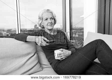 Senior woman using TV remote control on sofa at home