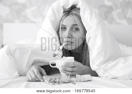 Portrait of sad woman with coffee mug taking temperature while wrapped in quilt on bed