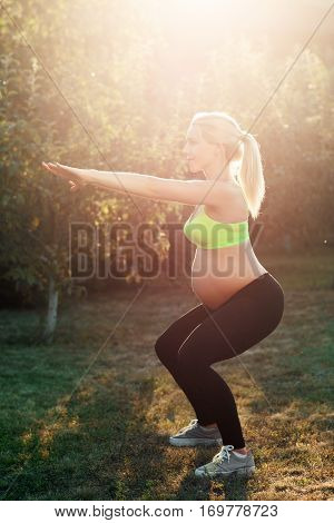 Pregnant woman squatting outdoor, sunrise light. Side view on expectant female in sportswear cowering early in morning. Health and body care, healthy lifestyle concept