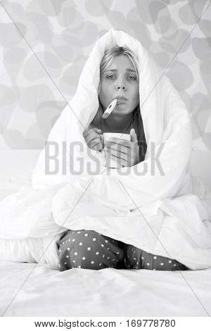 Portrait of young woman with coffee mug taking temperature while wrapped in quilt on bed