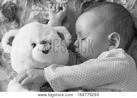 Newborn baby sleeps with a teddy bear black and white