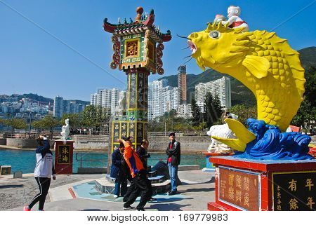 REPULSE BAY, HONG KONG - MARCH 02, 2016: People toss a coin into the fish's mouth the believe it good luck. MARCH 02, 2016