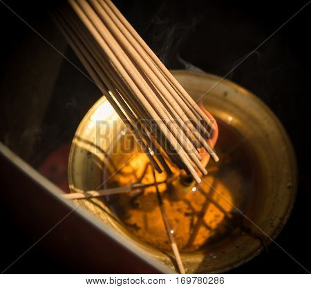 Photo of Smoke Sticks Burning Out in Gold Bowl with Fire. Asian Religion Aroma Sticks for Praying